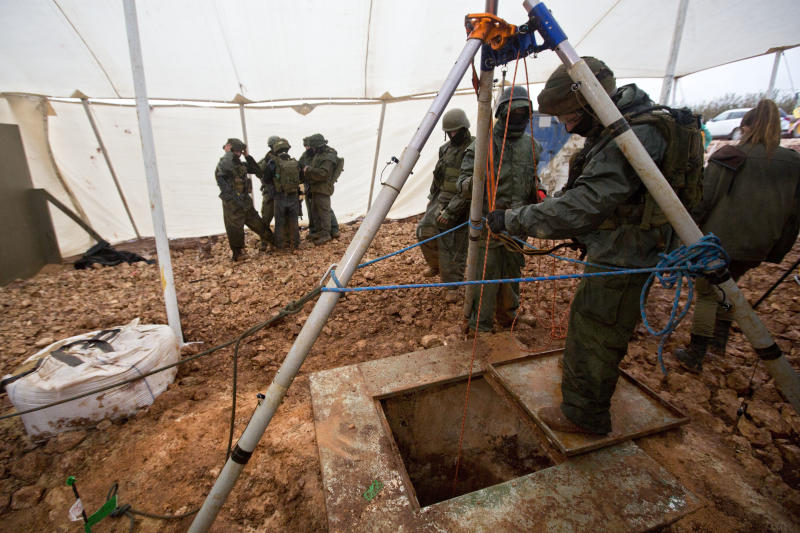 "File - In this Wednesday, Dec. 19, 2018 file photo, Israeli soldiers stand around the opening of a hole that leads to a tunnel that the army says crosses from Lebanon to Israel, near Metula. The Israel military says it has concluded ""Operation Northern Shield"" by uncovering the sixth and final Hezbollah attack tunnel from Lebanon. (AP Photo/Sebastian Scheiner, File)"