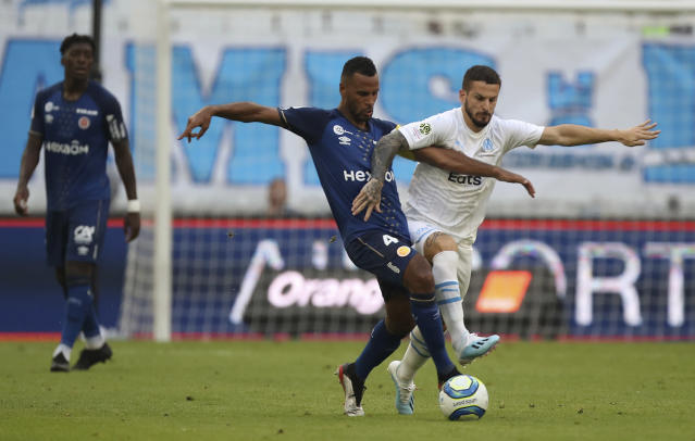 Marseille's Dario Benedetto, right, is challenged by Reims' Alaixys Romao during the French League One soccer match between Marseille and Reims at the Velodrome Stadium in Marseille, France, Saturday, Aug. 10, 2019. (AP Photo/Daniel Cole)