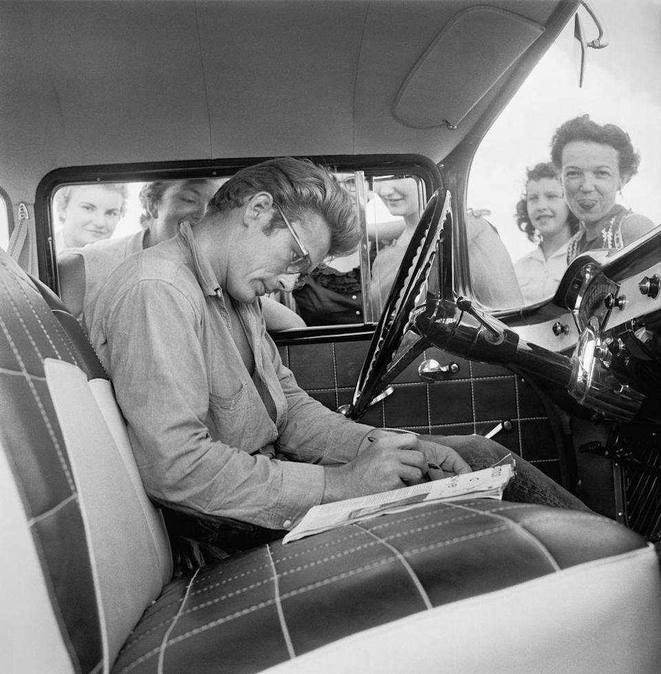 <p>Dean's car is stopped by fans for autographs while filming <em>Giant. </em>This was the third of Dean's major pictures, although at this time, only <em>East of Eden </em>had been released. </p>