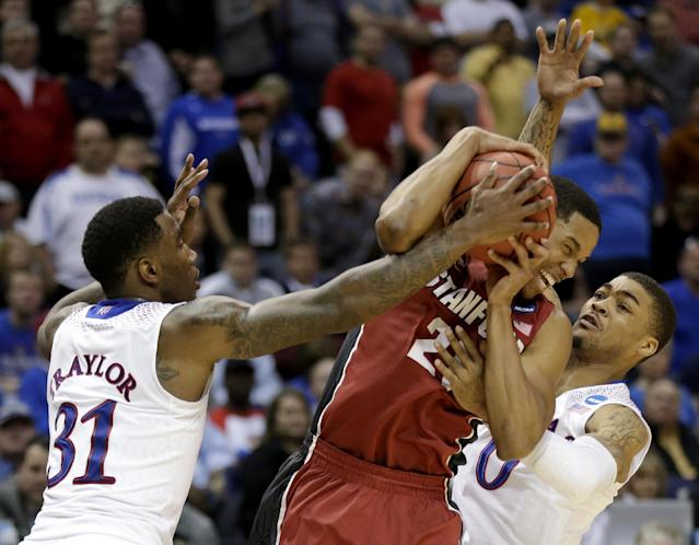 Kansas's Jamari Traylor (31) and Frank Mason (0) try to steal the ball from Stanford's Anthony Brown during the second half of a third-round game at the NCAA college basketball tournament Sunday, March 23, 2014, in St. Louis. Stanford won the game 60-57. (AP Photo/Charlie Riedel)