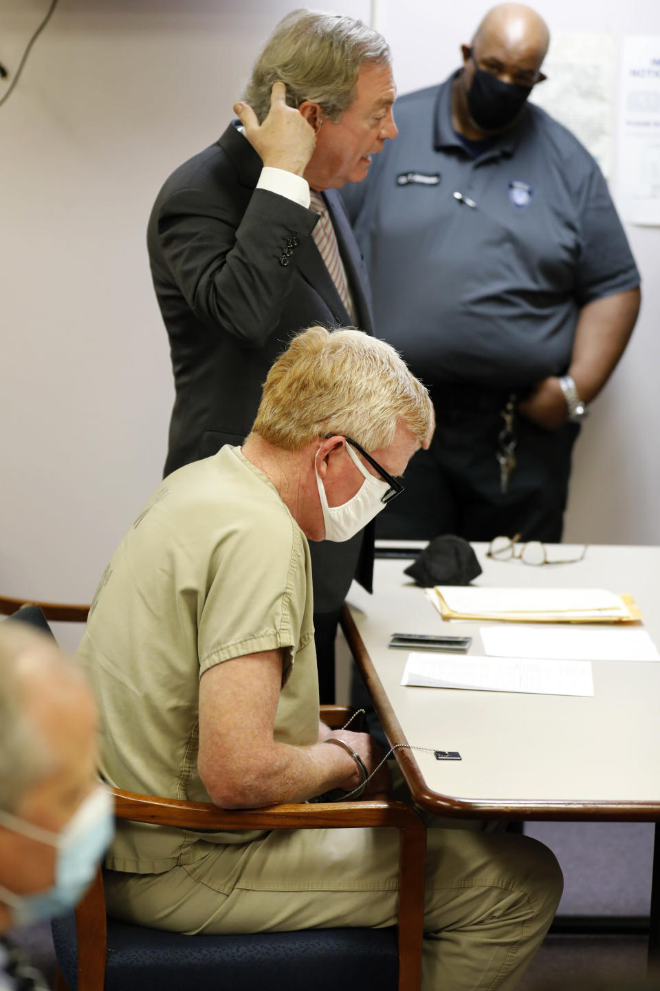 Alex Murdaugh's attorney Dick Harpootlian points to his head where Murdaugh, center, was shot in the head during Murdaugh's bond hearing, Thursday, Sept. 16, 2021, in Varnville, S.C. Murdaugh surrendered Thursday to face insurance fraud and other charges after state police said he arranged to have himself shot in the head so that his son would get a $10 million life insurance payout. (AP Photo/Mic Smith)