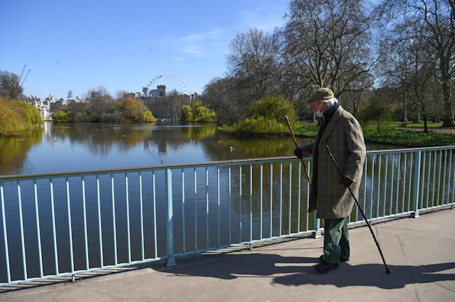 An elderly man walks in St James's Park, London, the day after Boris Johnson put the UK under emergency lockdown restrictions. (PA)