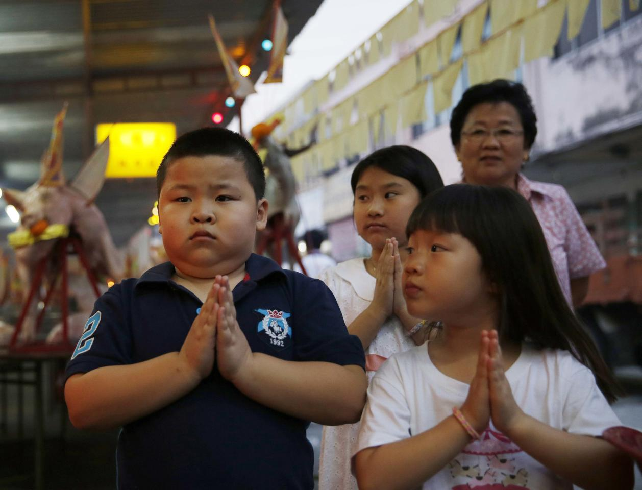 Children pray during the Hungry Ghost festival in Kuala Lumpur August 3, 2014. According to Taoist and Buddhist beliefs, the seventh month of the Chinese Lunar calendar, known as the Hungry Ghost Festival is when the Gates of Hell open to let out spirits who wander the land of the living looking for food. Food offerings are made while paper money and joss sticks are burnt to keep the spirits of dead ancestors happy and to bring good luck. REUTERS/Olivia Harris (MALAYSIA - Tags: SOCIETY RELIGION)