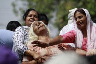 FILE - In this May 18, 2018, file photo, Indian women wail near the bodies of relatives, victims of cross-border firing, as they block a road during a protest in Ranbir Singh Pura, Jammu and Kashmir state, India. The Line of Control, a highly militarized de facto border that divides the disputed region between the two nuclear-armed rivals India and Pakistan, and a site of hundreds of deaths, is unusually quiet after the two South Asian neighbors agreed in February, 2021, to reaffirm their 2003 cease-fire accord. (AP Photo/Channi Anand, File)