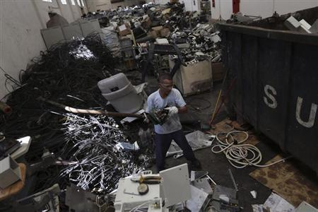 An employee holds circuit boards at the Coopermiti warehouse of electronic waste in Sao Paulo