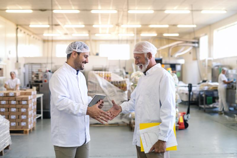 Two uniformed workers shake hands in a food manufacturing facility.