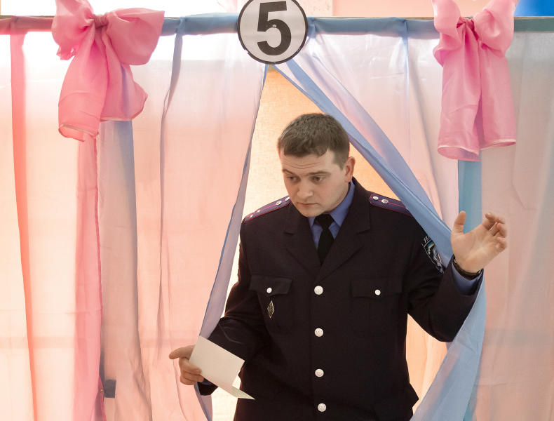 An Ukrainian policeman exits a voting booth after casting his vote in Perevalne, Ukraine, Sunday, March 16, 2014. Residents of Ukraine's Crimea region are voting in a contentious referendum on whether to split off and seek annexation by Russia. (AP Photo/Vadim Ghirda)