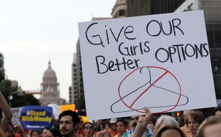Protesters carry signs during an abortion rights march that originated at the State Capitol in Austin, Texas, in this file photo taken July 8, 2013. REUTERS/Mike Stone/Files