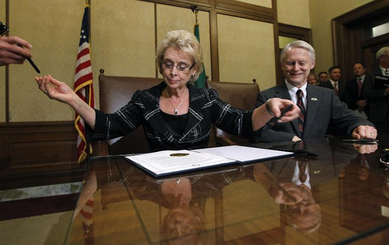 As Secretary of State Sam Reed, right, looks on, Gov. Chris Gregoire hands off one pen and reaches for another as she goes through a stack of them while signing Referendum 74, a citizen-passed measure that legalizes same-sex marriage in the state, Wednesday, Dec. 5, 2012, in Olympia, Wash. Gregoire and Reed both signed the document at the ceremony, which allows gay couples to marry beginning Dec. 9. (AP Photo/Elaine Thompson)
