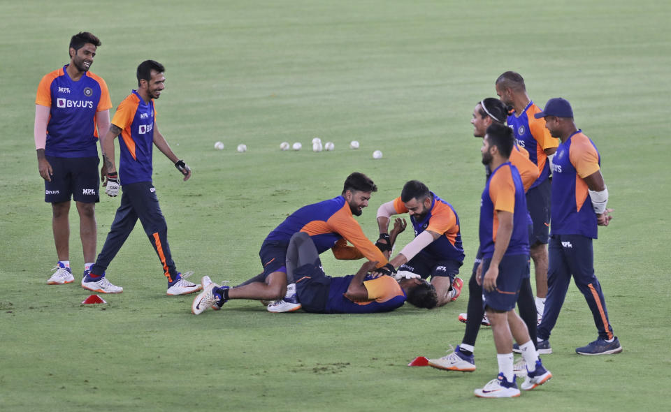 Indian cricket team captain Virat Kohli, sitting right, with Rishabh Pant, center, shares a lighter moment with a team support staff as others watch during a training session ahead of the first Twenty20 cricket match between India and England in Ahmedabad, India, Tuesday, March 9, 2021. (AP Photo/Aijaz Rahi)