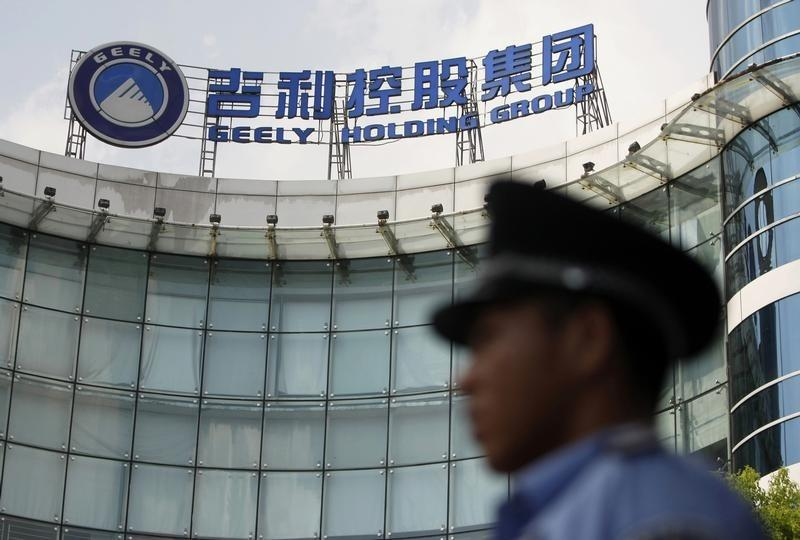 A security personnel on duty stands in front of the headquarters of Zhejiang Geely Holding Group in Hangzhou