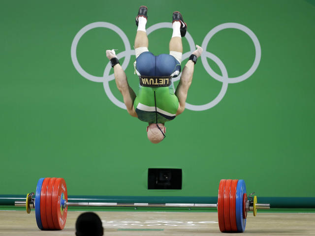 <p>Aurimas Didzbalis, of Lithuania, does a flip after his final lift of the night in the men's 94kg weightlifting competition at the 2016 Summer Olympics in Rio de Janeiro, Brazil, Saturday, Aug. 13, 2016. (AP Photo/Mike Groll) </p>
