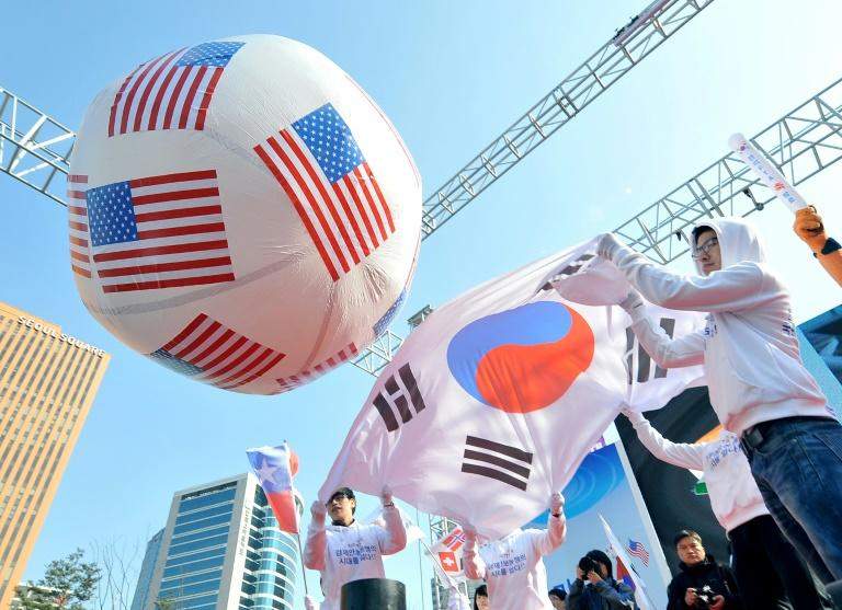 South Korean conservative activists roll a large balloon showing the US flags by a South Korean flag during a rally to support South Korea-US free trade agreement in Seoul in 2012