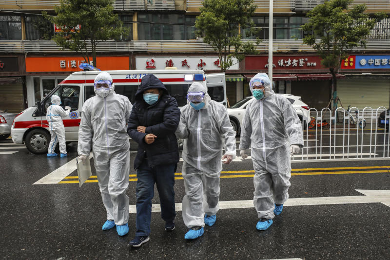 FILE - In this Sunday, Jan. 26, 2020 file photo, medical workers in protective gear help a patient near an ambulance in Wuhan in central China's Hubei Province.As Beijing instates one of the largest quarantines in modern history, locking down over 50 million people in Hubei province, questions are swirling around the provincial government's sluggish initial response. (Chinatopix via AP, File)