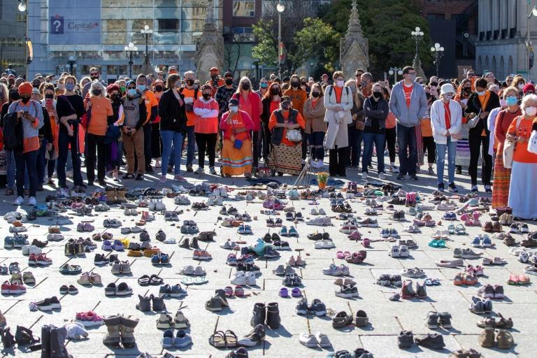 A crowd gathers outside parliament in Ottawa around shoes that honour missing and deceased indigenous children during Canada's first National Day for Truth and Reconciliation (AFP/Lars Hagberg)