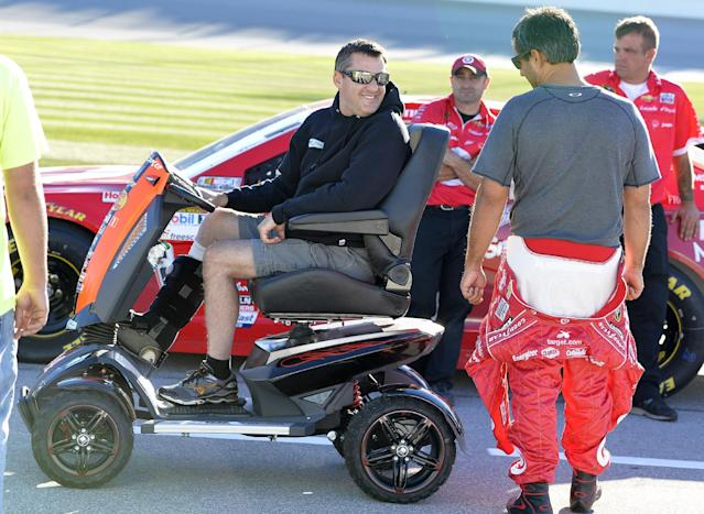 NASCAR driver Tony Stewart, left, in a motorized scooter, talks with Juan Pablo Montoya,of Colombia, during qualifying for Sunday's NASCAR Sprint Cup Series auto race at Chicagoland Speedway in Joliet, Ill., Friday, Sept. 13, 2013. Stewart fractured his tibia and fibula in sprint car race in Iowa on Aug. 5, 2013. (AP Photo/Nam Y. Huh)