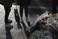 People stand near flowers, messages and candles outside Notre Dame church, in Nice, France, Friday, Oct. 30, 2020. A new suspect is in custody in the investigation into a gruesome attack by a Tunisian man who killed three people in a French church. France heightened its security alert amid religious and geopolitical tensions around cartoons mocking the Muslim prophet. (AP Photo/Daniel Cole)