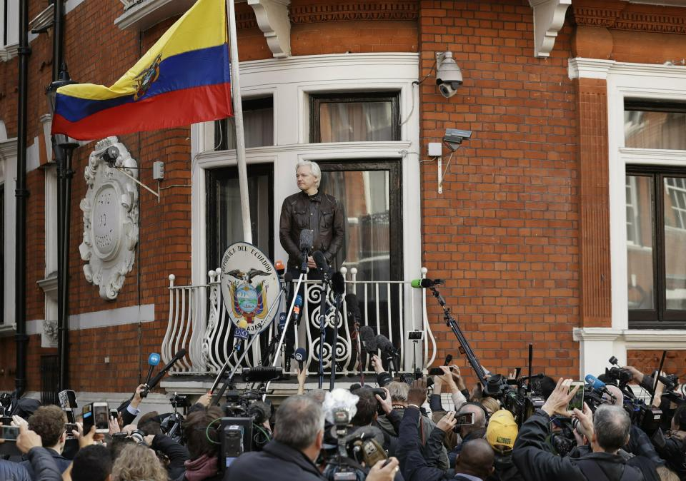 Watched by the media WikiLeaks founder Julian Assange looks out from the balcony of the Ecuadorian embassy prior to speaking, in London on May 19, 2017. (Matt Dunham/AP)