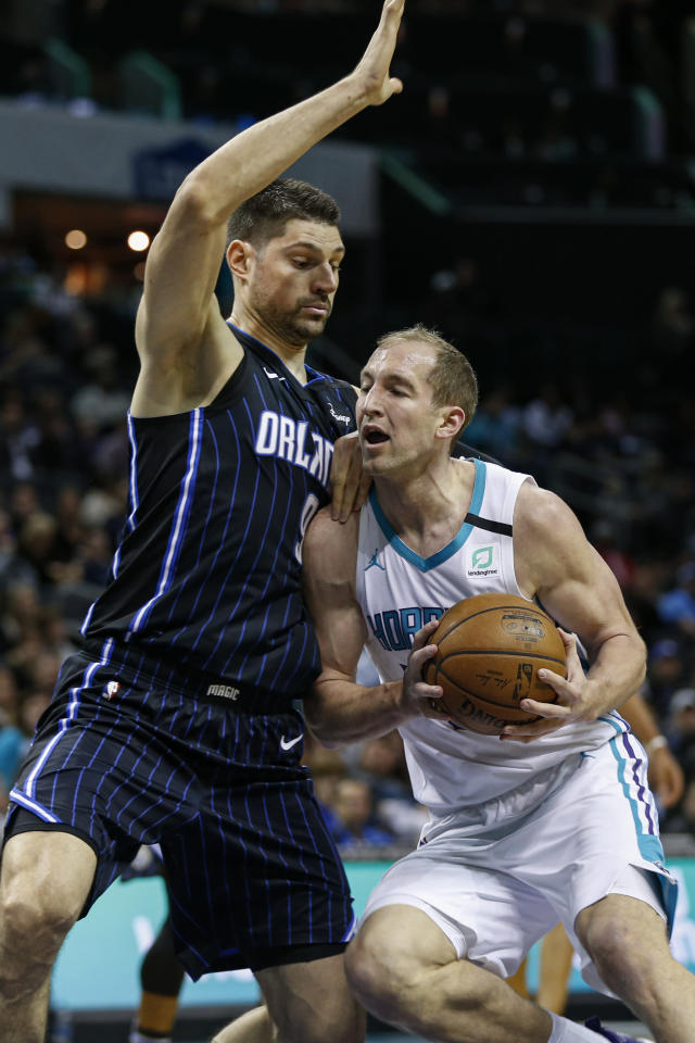 Charlotte Hornets forward Cody Zeller, right, drives into Orlando Magic center Nikola Vucevic in the first half of an NBA basketball game in Charlotte, N.C., Monday, Jan. 20, 2020. (AP Photo/Nell Redmond)