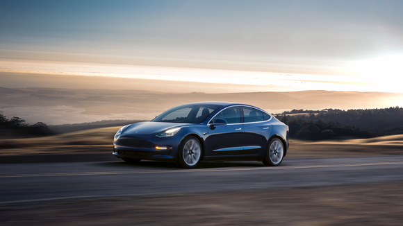 Blue Model 3 driving along a coastal road