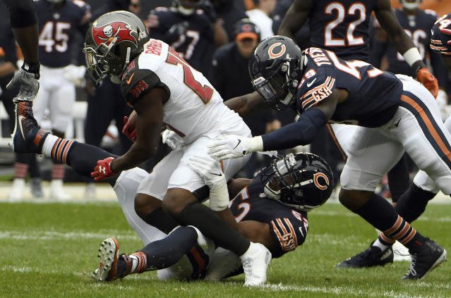 Chicago Bears linebacker Khalil Mack (52) tackles Tampa Bay Buccaneers running back Peyton Barber (25) as Chicago Bears linebacker Danny Trevathan (59) approaches them during the first half of an NFL football game Sunday, Sept. 30, 2018, in Chicago. (AP Photo/David Banks)