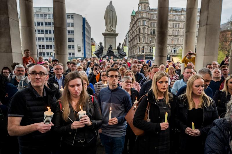 People hold candles during a vigil at Belfast City Hall in memory of murdered journalist Lyra McKee (PA)