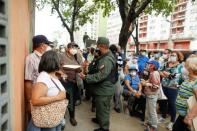 A woman argues with a Bolivarian National Guard Soldier, as senior citizens and health workers wait to receive their first dose of Russia's Sputnik V vaccine against the coronavirus disease (COVID-19), in Caracas