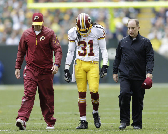 Washington Redskins' Brandon Meriweather is helped off the field during the first half of an NFL football game against the Green Bay Packers Sunday, Sept. 15, 2013, in Green Bay, Wis. (AP Photo/Tom Lynn)
