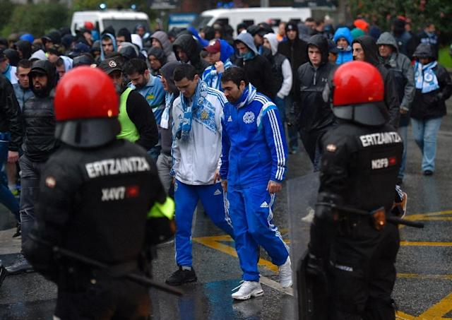 High tension: Marseille fans walk past Basque autonomous police officers outside the San Mames stadium before the Europa League match against Athletic Bilbao (AFP Photo/ANDER GILLENEA)