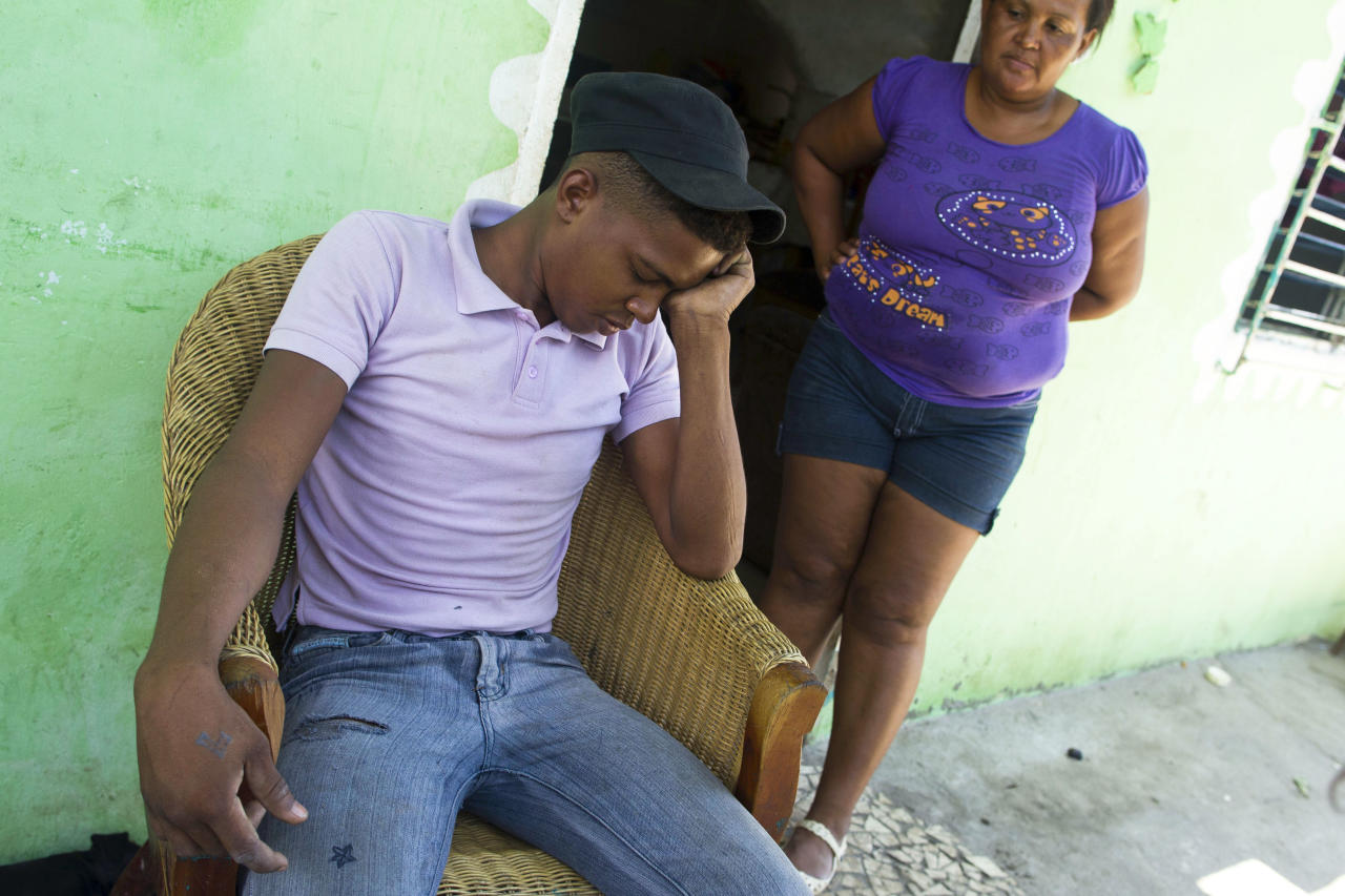 Adrian Vasquez, left, sits next to his mother, Nilsa De La Cruz, 42, right, for an interview with the Associated Press outside his home in the town of Rio Hato, Panama, Thursday, April 19, 2012. Vasquez, an 18-year-old Panamanian, went on a fishing trip with two friends last Feb. 24 but while returning home, their motor died. They had been drifting for 16 days when birdwatchers with powerful spotting scopes on the deck of the luxury cruise ship Star Princess saw their boat adrift miles away and told ship staff about a man desperately waving a red cloth. The cruise ship didn't stop, and the fishing boat drifted another two weeks before it was found. By then, Vasquez's two friends had died. (AP Photo/Tito Herrera)