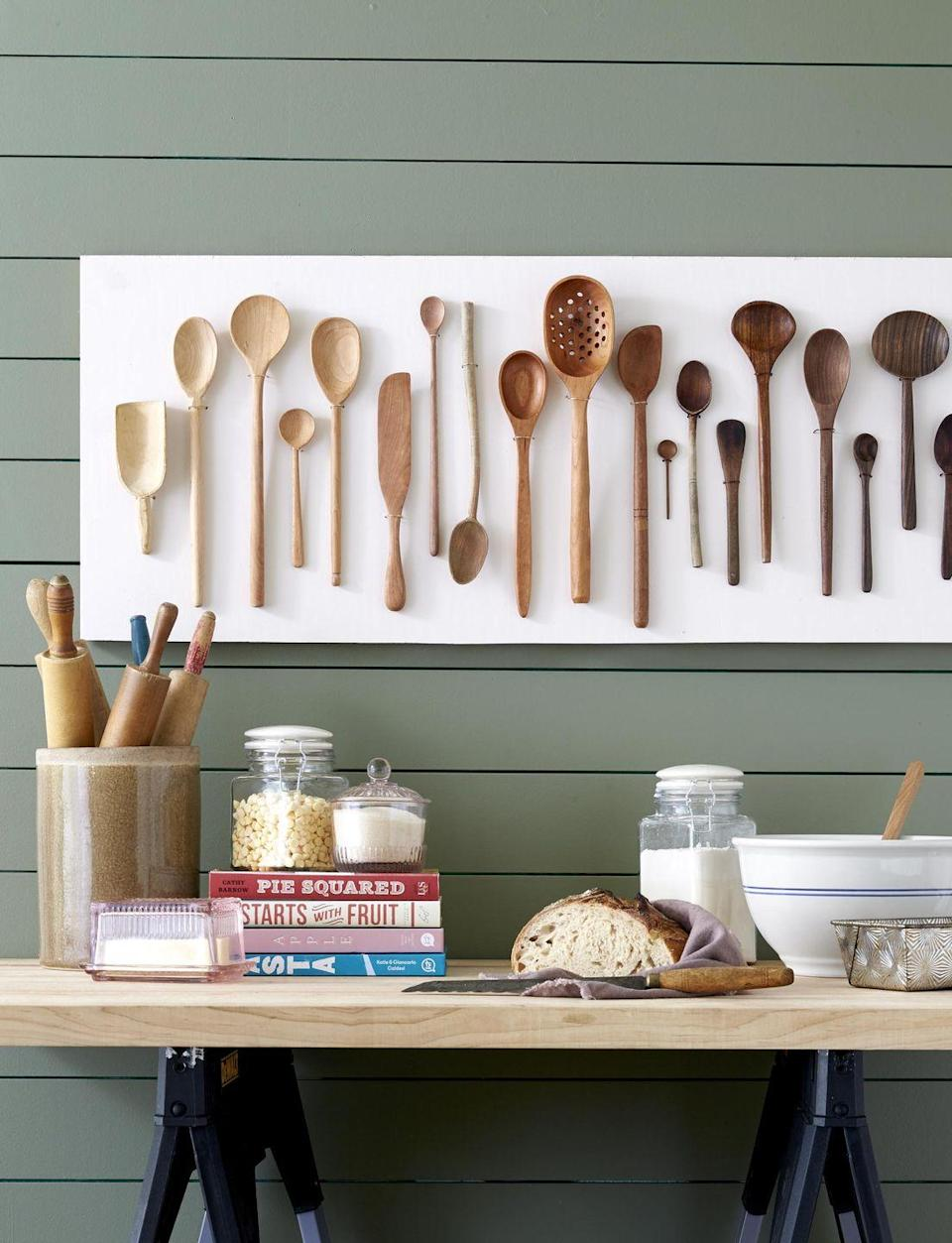 <p>A collection of spoons takes pride of place in the kitchen when mounted on a painted board. For an extra special look, mount them in an ombre pattern.<br><br><strong>To make: </strong>To assemble, cut a piece of plywood to the desired size and paint. Lay spoons in a light-to-dark pattern on the wood, and use a pencil to mark a spot on both sides of each spoon, typically<br>just below the bowl. Remove spoons, and drill holes at markings. Working with one spoon at a time, loop fine-gauge wire over the handle and through the holes; twist together wire ends behind the wood to secure. Repeat until complete, then hang.</p>