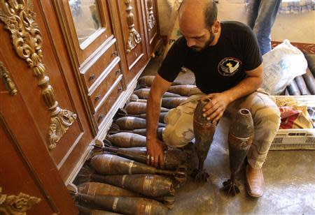 A Free Syrian Army handles homemade mortar shells inside a house in the old city of Aleppo