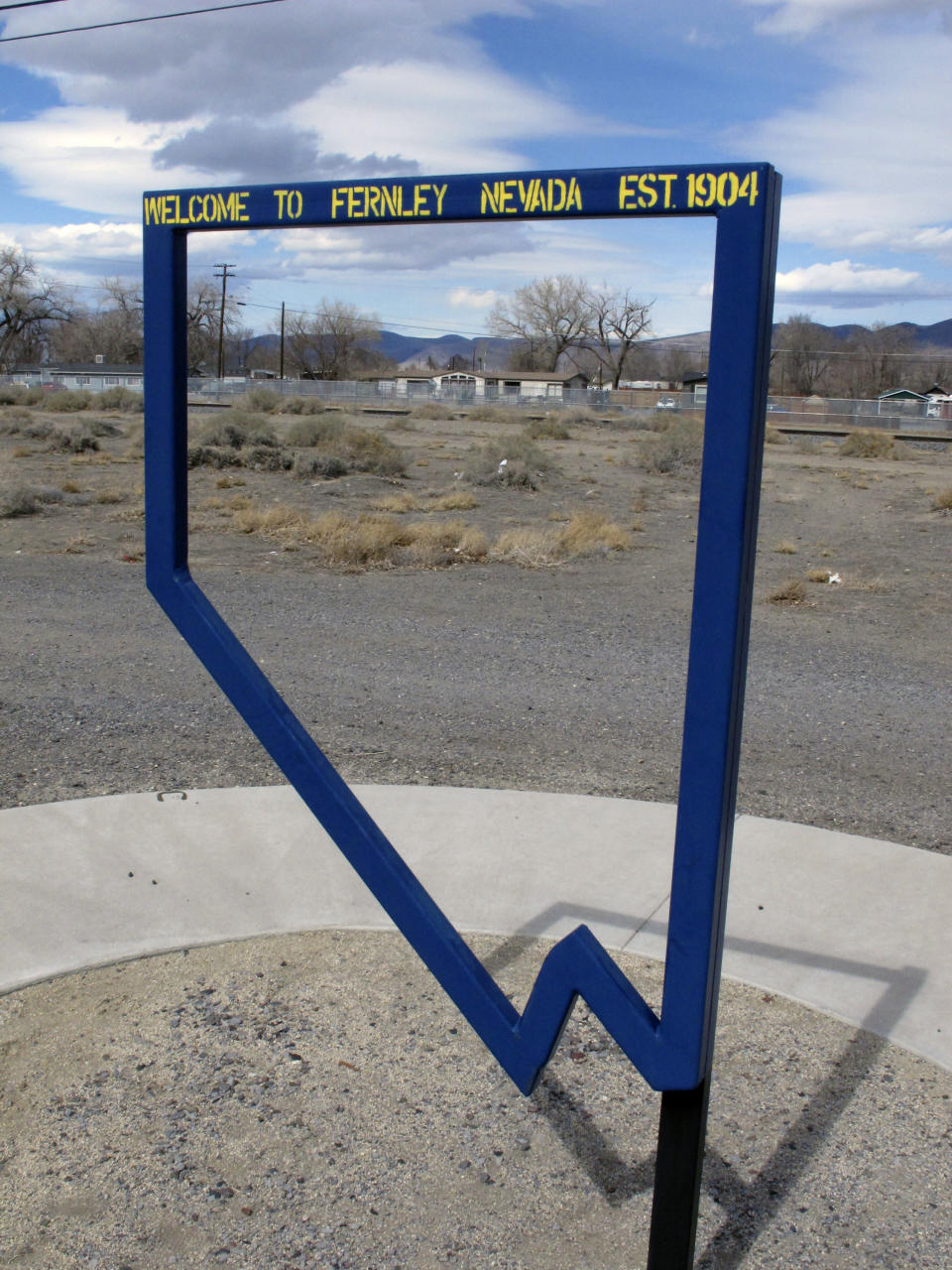 This Thursday, March 18, 2021 photo in Fernley, Nev. shows a sign at a park marking the founding of the town about 30 miles east of Reno in 1905. The founders were lured to the West with the promise of free land and cheap water. Now, the city is suing the U.S. government over plans to renovate an earthen irrigation canal that burst and flooded nearly 600 homes in in 2008. (AP Photo/Scott Sonner)