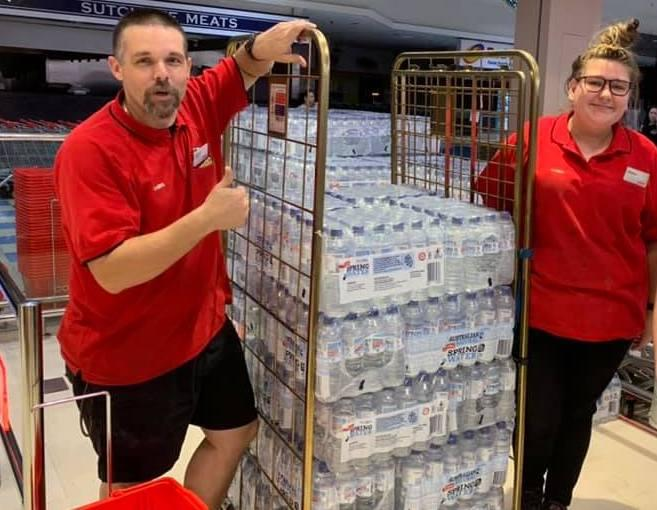 Coles workers loading up bottled water for rural fire services.
