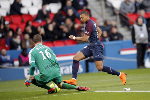 PSG's Kylian Mbappe, right, challenges with Angers' Ludovic Butelle during the French League One soccer match between Paris Saint-Germain and Angers at the Parc des Princes Stadium, in Paris, France, Wednesday, March 14, 2018. (AP Photo/Christophe Ena)