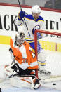 Buffalo Sabres' Curtis Lazar, rear, looks at the puck after scoring a goal past Philadelphia Flyers goaltender Carter Hart during the first period of an NHL hockey game, Monday, Jan. 18, 2021, in Philadelphia. (AP Photo/Derik Hamilton)