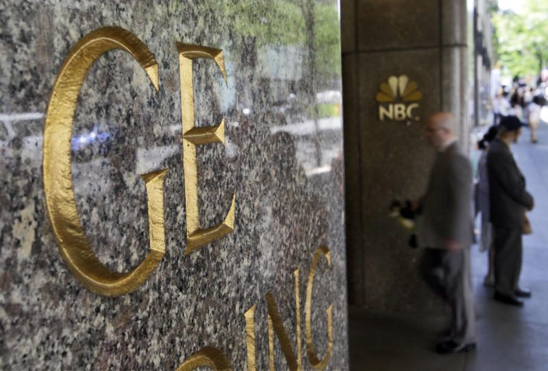 "FILE - In this file photo made July 15, 2009, General Electric and NBC logos adorn the GE Building in New York's Rockefeller Center. Comcast said Tuesday that it's buying General Electric's 49 percent stake in the NBCUniversal joint venture for $16.7 billion several years early, as the company takes advantage of low borrowing costs and what CEO Brian Roberts called a ""very attractive price."" (AP Photo/Richard Drew, File)"