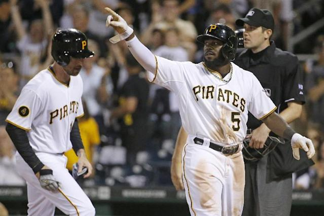 Pittsburgh Pirates' Josh Harrison (5) points to teammate Russell Martin on second after scoring on Martin's three-run double off Milwaukee Brewers relief pitcher Tyler Thornburg during the sixth inning of a baseball game in Pittsburgh Friday, June 6, 2014. (AP Photo/Gene J. Puskar)