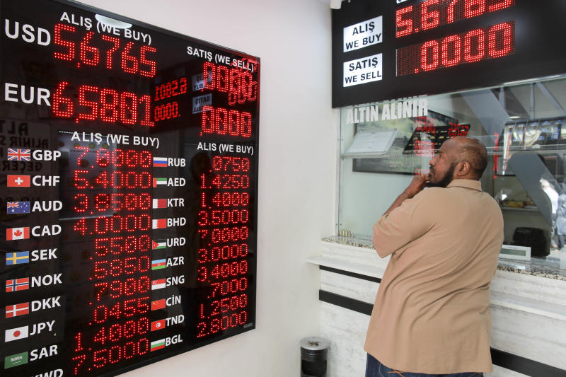 A man checks foreign currency exchange rates outside a currency exchange shop in an Istanbul's market, Friday, Aug. 10, 2018. A financial shockwave ripped through Turkey on Friday as its currency nosedived on concerns about its economic policies and a dispute with the U.S., which President Donald Trump stoked further with a promise to double tariffs on the NATO ally. . (AP Photo/Mucahid Yapici)