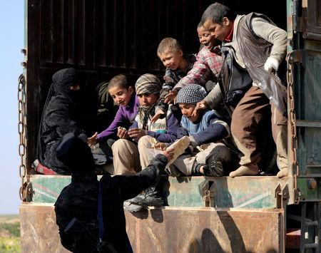 FILE PHOTO: A fighter from the Syrian Democratic Forces (SDF) gives bread to children near the village of Baghouz
