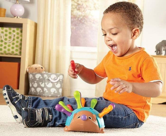 """This helps kids build motor, counting and sorting skills by fitting peg-shaped pieces into its back. Just don't ask him if he knows Sonic.<br /><br /><strong>Promising Review:</strong>""""Love this product. It says 18+ months but it was fun for both of my kids (11 months and 3). It's meant to help with fine motor skills.<strong>The spikes are rubber with different colors and you can put them in and take them out of the holes in the hedgehog.</strong>The best part is that when they're done playing the hedgehog opens and you can store all the spikes in there so they don't get lost."""" —<a href=""""https://amzn.to/3erFlky"""" target=""""_blank"""" rel=""""noopener noreferrer"""">Tony Wexler</a><br /><strong><br />Get it from Amazon for<a href=""""https://amzn.to/3tJrMDI"""" target=""""_blank"""" rel=""""noopener noreferrer"""">$9.59</a>.</strong>"""