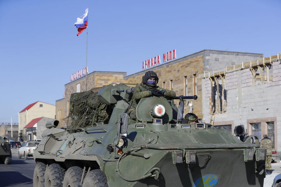 Russian military vehicles roll along a road in Martuni, Armenia, towards the separatist region of Nagorno-Karabakh, Friday, Nov. 13, 2020. Dozens of Russian peacekeepers destined for Nagorno-Karabakh have begun deploying hours after Armenia and Azerbaijan agreed to halt fighting over the separatist region. (AP Photo/Sergei Grits)