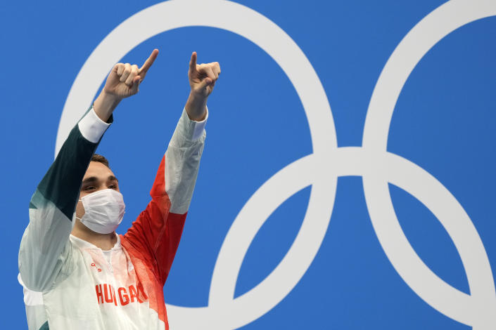 Kristof Milak of Hungary waves on the podium after winning the gold medal in the men's 200-meter butterfly final at the 2020 Summer Olympics, Wednesday, July 28, 2021, in Tokyo, Japan. (AP Photo/Martin Meissner)