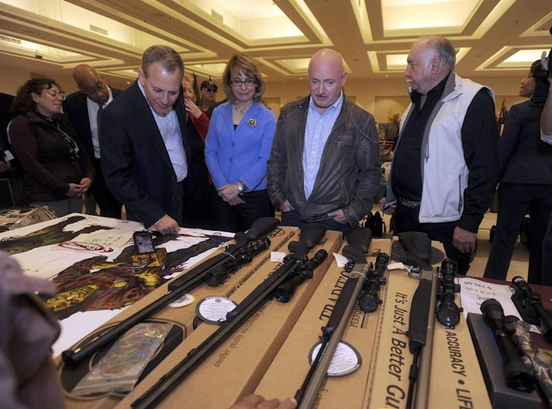 New York Attorney General Eric Schneiderman, left, former Arizona congresswoman Gabrielle Giffords, second from left, and her husband Mark Kelly, second from right, along with show organizer Dave Petronis tour the New EastCoast Arms Collectors Associates arms fair in Saratoga Springs, N.Y. on Sunday, Oct. 13, 2013. They are looking at a display of muzzle loaders. (AP Photo/Tim Roske, Pool)
