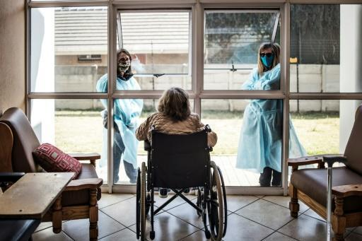 Relatives in protective gear chat to a resident through a window to reduce the risk of virus infection