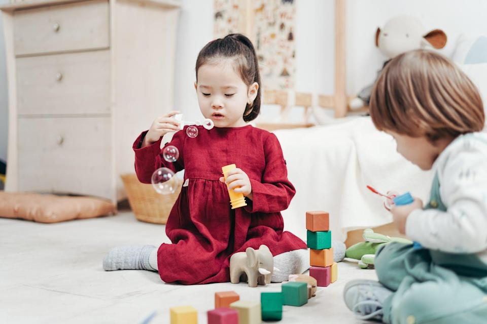Children play with bubbles and blocks.