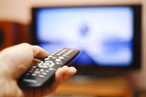 A person pointing a remote control at a television.