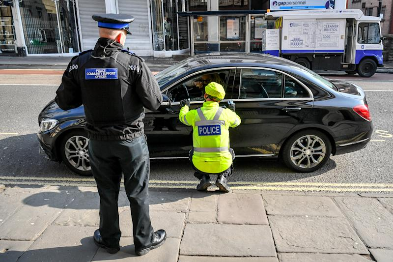 Police stop motorists as they travel on Park Street, Bristol, where random checks on essential travel are taking place as the UK continues in lockdown to help curb the spread of the coronavirus.