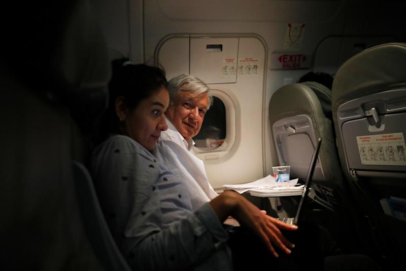 Mexican President Andres Manuel Lopez Obrador sits next to an assistant as he travels in economy class aboard a commercial flight from Guadalajara to Mexico City, on Saturday, March 9, 2019. Lopez Obrador has answered more questions from the press, flown in more economy-class flights, posed for more selfies with admiring citizens and visited more genuinely risky areas with little or no security than several combined decades of his predecessors.(AP Photo/Marco Ugarte)
