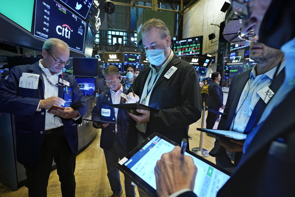 Traders gather at a post on the floor of the New York Stock Exchange, Tuesday, Aug. 3, 2021. Stocks are off to a mixed start on Wall Street as traders weigh another big set of company earnings reports, which have been coming in largely ahead of analysts' forecasts. (AP Photo/Richard Drew)